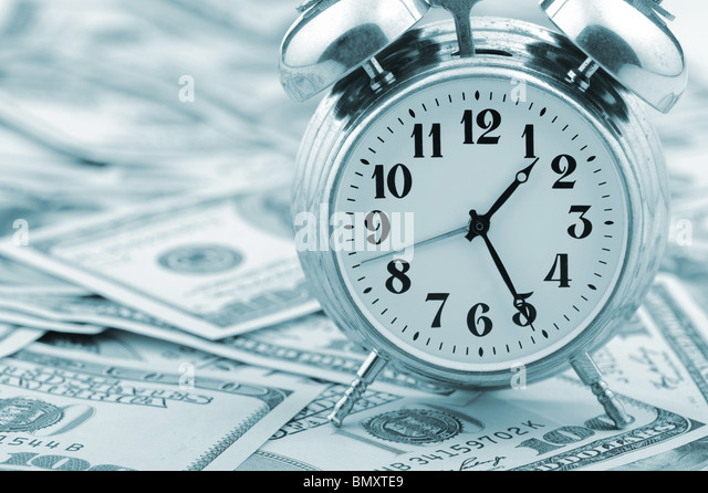 Time - money. Business concept. Analog hours on a heap of paper dollars. Blue tone - Stock Image