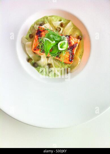 Salmon entree seasoned with fennel served in a bright contemporary white dish. - Stock Image