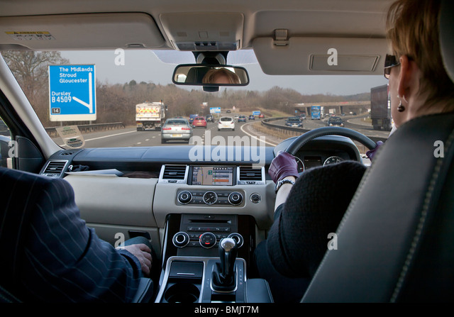 Interior of Range Rover car being driven by woman on motorway in UK, man passenger, with sat nav on dashboard and - Stock Image