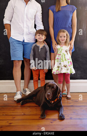 Cropped shot of lovely young family with their pet dog. Labrador retriever sitting on floor with kids and their - Stock Image