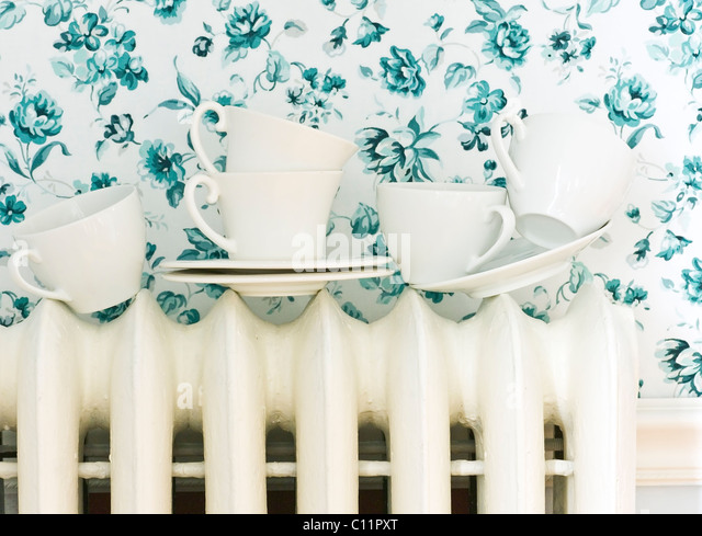 Tea Cups on Radiator with Blue Flowered Background - Stock Image