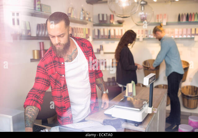Owner standing at checkout counter while customers shopping in background - Stock-Bilder