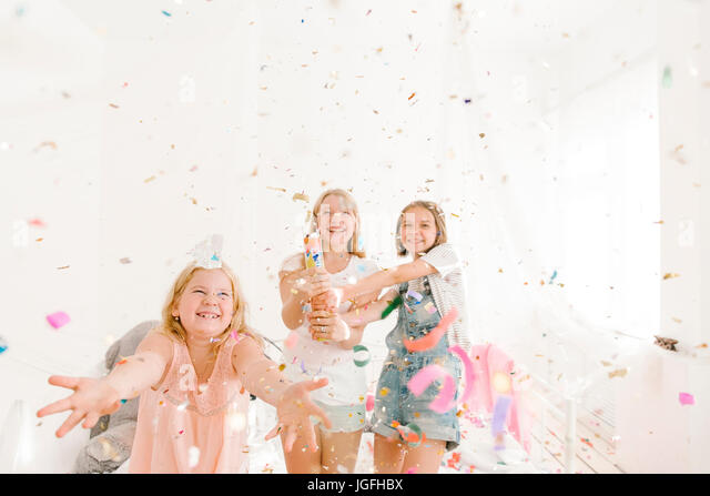 Smiling Middle Eastern girls throwing confetti in bedroom - Stock Image