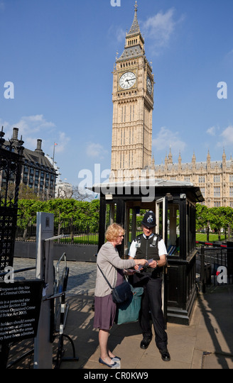 A policeman gives information to a female tourist, House of Parliament, London, England, UK - Stock Image
