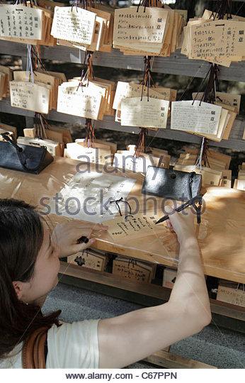 Japan Tokyo Shibuya-ku Meiji Jingu Shinto Shrine ema wooden tablets wishes prayers kanji hiragana characters Japanese - Stock Image