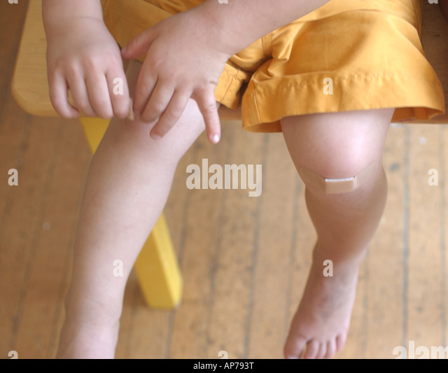 young child puts band aid on his knees caring for himself growth ouch - Stock Image