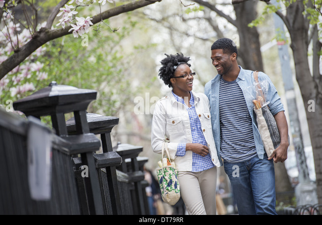 A couple walking in the park side by side carrying shopping bags. - Stock Image
