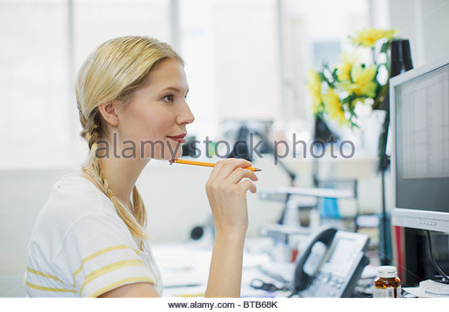 Businesswoman holding pencil and looking at computer monitor - Stock Image