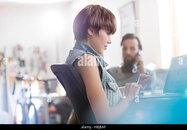 Female design professional working at laptop in office - Stock-Bilder