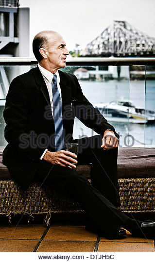 Senior Executive Sitting On A Waterfront House Verandah Looking Out To The Distance With A Positive Future Outlook, - Stock Image