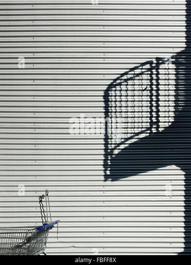 Cropped Shopping Cart Against Shutter - Stock Image