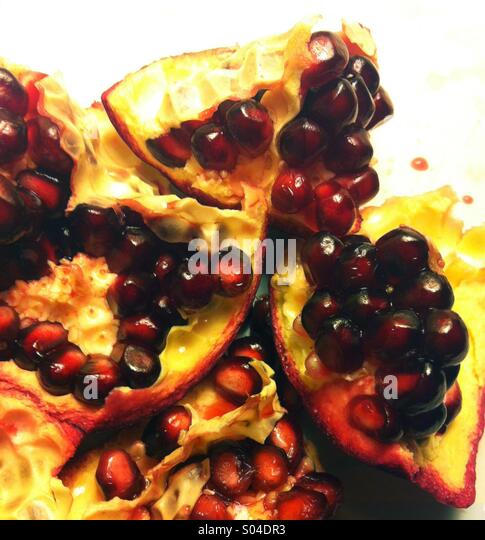 An open pomegranate fruit shows its red seeds. - Stock Image