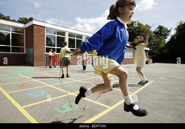 Schoolgirls skipping in a primary school playground in the UK. - Stock Image