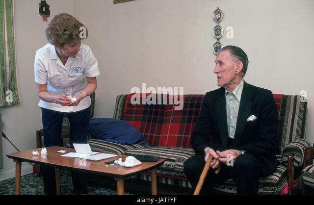 community nurse assisting elderly man in sheltered accommodation - Stock Image