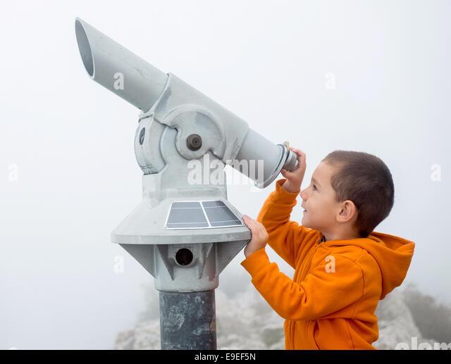 Boy looking into the sky through a monocular - Stock Image