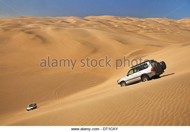 Namib-Naukluft National Park Namibia Off-road vehicles crossing sand dunes Namibia - Stock Image