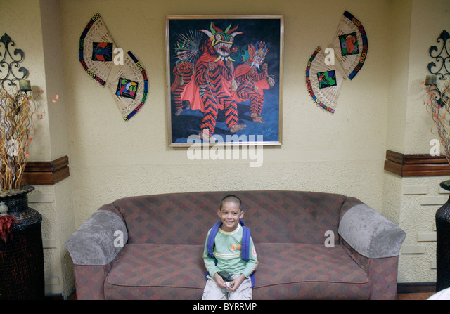 Panama City Panama Bella Vista Via Espana Hotel California lobby Hispanic boy child sitting couch sofa decor painting - Stock Image