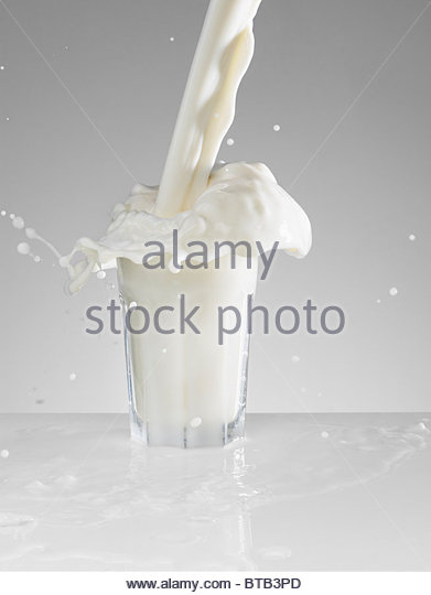 Milk splashing in full glass - Stock Image