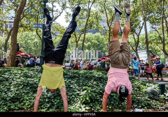 New York New York City NYC Manhattan Midtown Bryant Park public park upper terrace man doing handstand - Stock Image