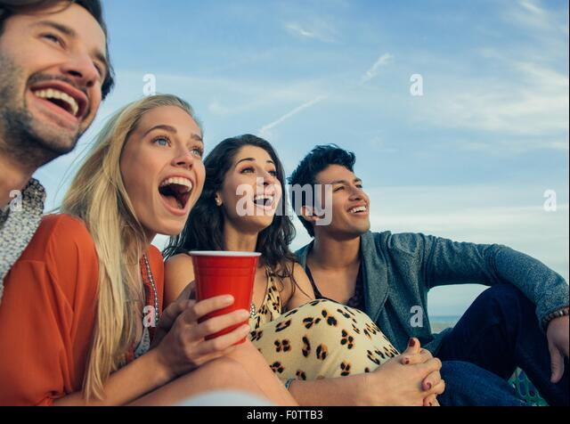 Group of friends sitting together outdoors, laughing - Stock Image
