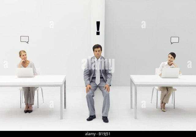 Man sitting in office with exclamation mark over his head, women on either side with blank word bubbles - Stock Image