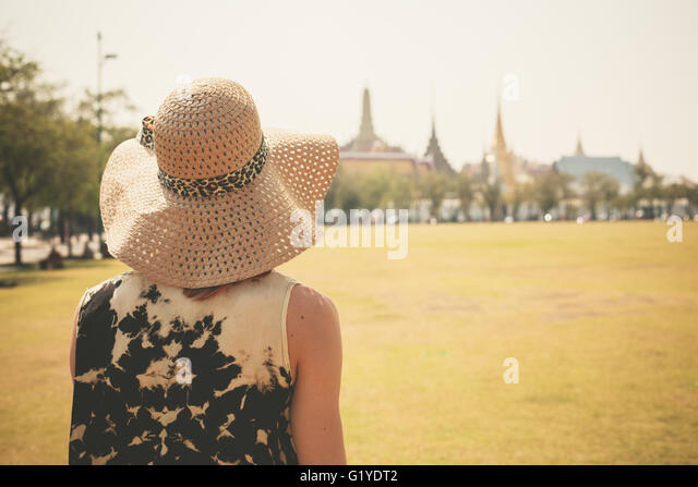 A young woman is standing in a park near the royal palace in Bangkok Thailand - Stock Image