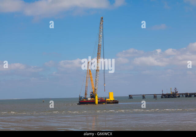 Hooksiel, North Sea, Germany, June 10. 2016, swimming construction crane at work - Stock Image