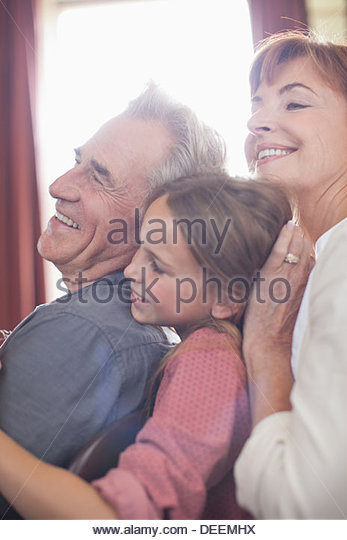 Happy grandparents and granddaughter hugging - Stock Image