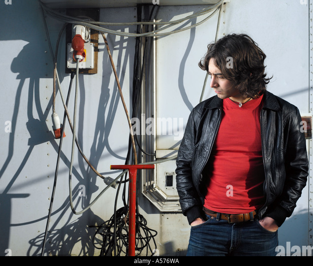 Young man in  black leather jacket standing amongst cables and pipework - Stock Image