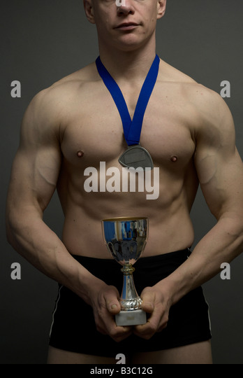A muscular man clutching trophy and wearing medal - Stock Image