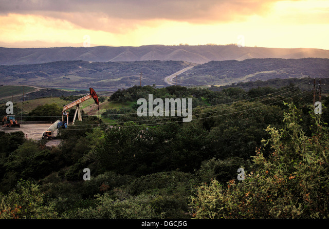 Derricks in oil well in rural landscape, California - Stock Image