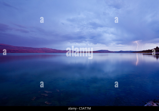 Lightning strike over lake at sunset. - Stock Image