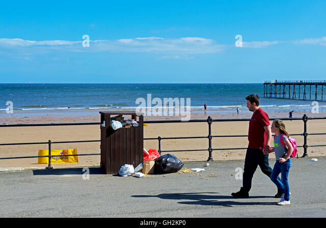 Man and young girl walking past overflowing rubbish bin on the promenade at Saltburn, North Yorkshire, England UK - Stock Image