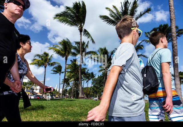 Miami Florida Beach Ocean Drive Lummus Park family walking mother father teen boy - Stock Image