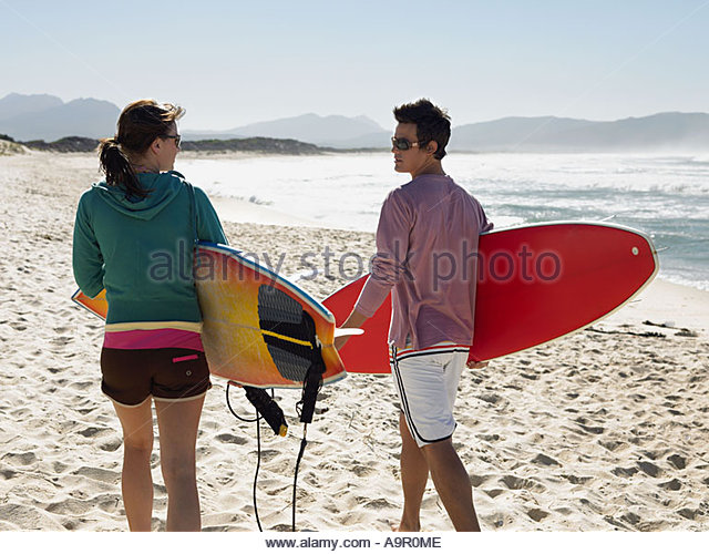 Couple going surfing - Stock Image
