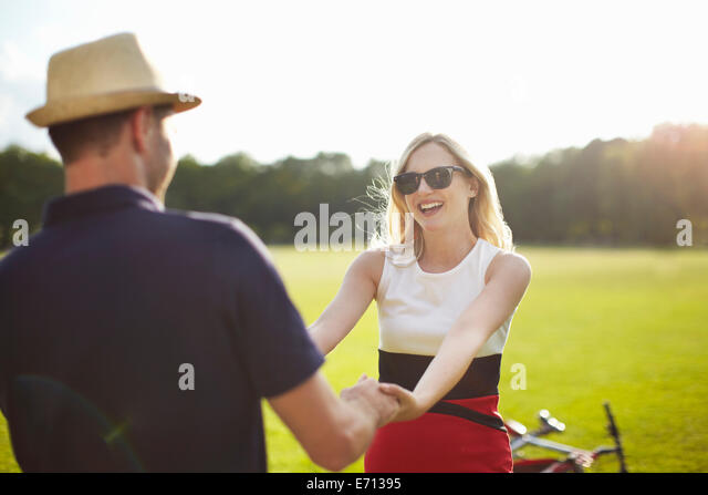 Couple holding hands and swirling each other around in park - Stock-Bilder
