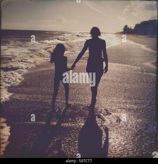 Mother and daughter walking on a Florida beach - Stock Image