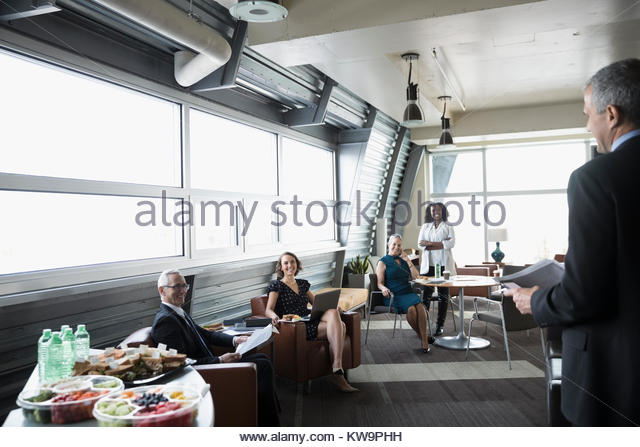 Businessman talking to colleagues,leading meeting in business lounge - Stock Image