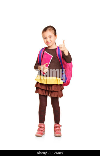 Full length portrait of a school girl with backpack holding book and showing thumb up - Stock Image