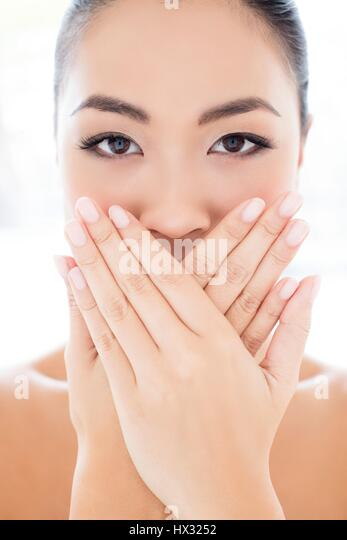 MODEL RELEASED. Young Asian woman with hands touching covering mouth, portrait. - Stock-Bilder