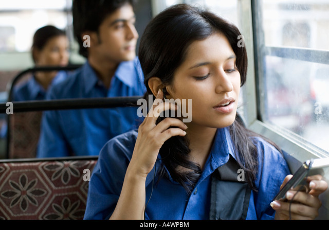 Female student listening to mp3 player on bus - Stock Image