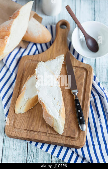 Bread with butter on cutting board - Stock Image