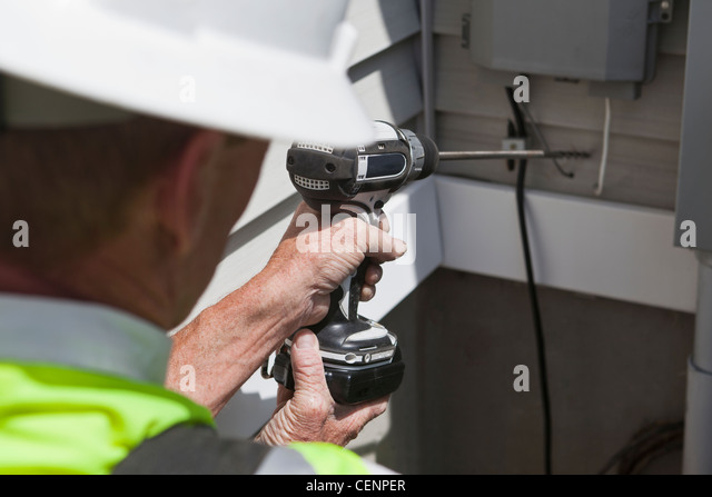 Communications worker drilling access hole through exterior wall - Stock-Bilder