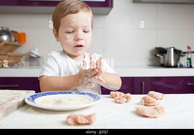 Baby boy preparing meatballs. He is kneading the balls - Stock Image