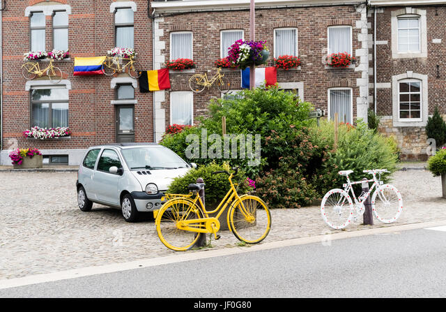HENRI-CHAPELLE, BELGIUM, 25th JUNE, 2017 - painted bicycles fixed on a pole near a street - Stock Image