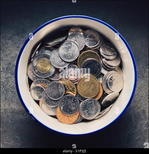 An overhead shot of a bowl full of assorted Canadian coins - Stock Image