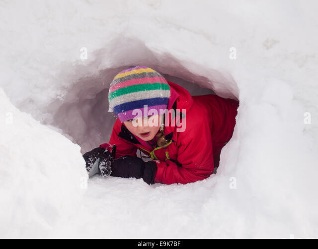 small girl in winter clothes playing in a snow hole - Stock Image