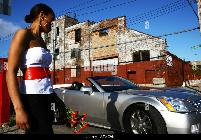 SOPHISTICATED YOUNG WOMAN HOLDING FLOWERS.  CONVERTIBLE CADILLAC CAR IN THE BACKGROUND - Stock Image