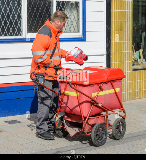 Postman and his red wheeled cart. - Stock Image
