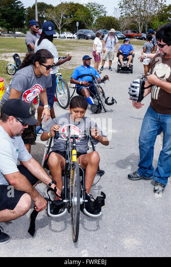 Florida FL Miami Tropical Park Paralympic Experience sports volunteer helping Hispanic teen boy disabled hand cycle - Stock Image
